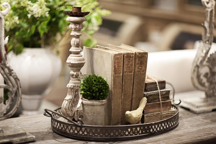 here a group of books ties together candlesticks and a little pot and