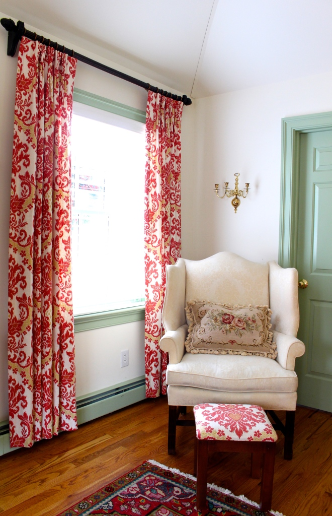 Williamsburg bedroom,, with oriental rug cream wing chair, ikat drapes, williamsburg green trim.