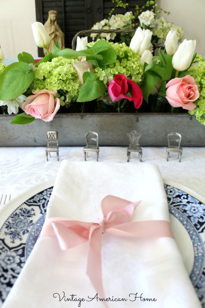 Bridal shower tablescapes for a blush pink themed wedding with antique navy blue and white plates with centerpieces.