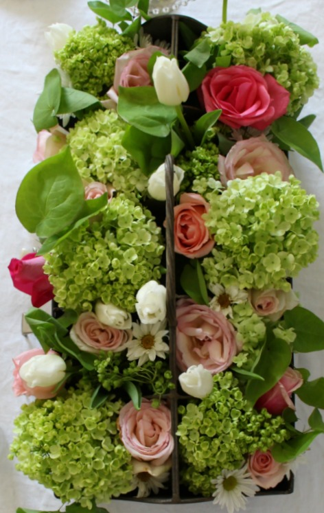 Roses, viburnum and epimedium centerpiece in 10 compartment cubby