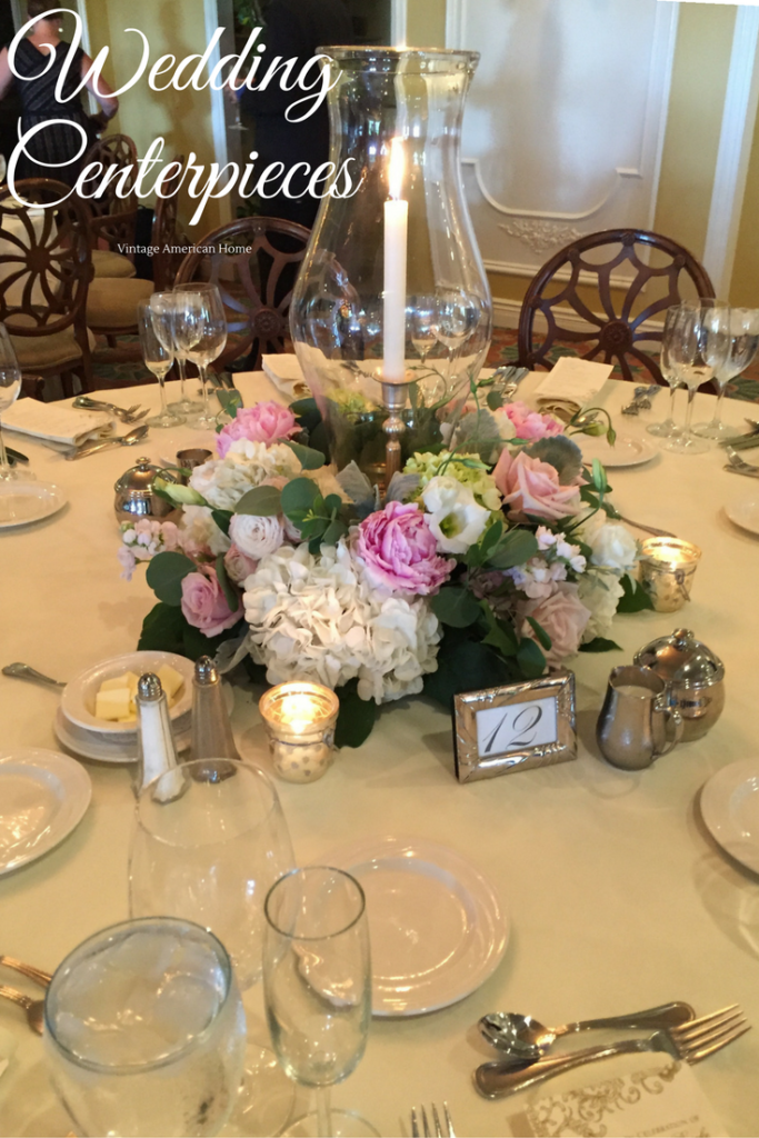 WEdding Centerpieces with peony, rose and hydrangea wreath surrounding Williamsburg hurricaine and single taper candle in silver candlestick from Vintage American Home