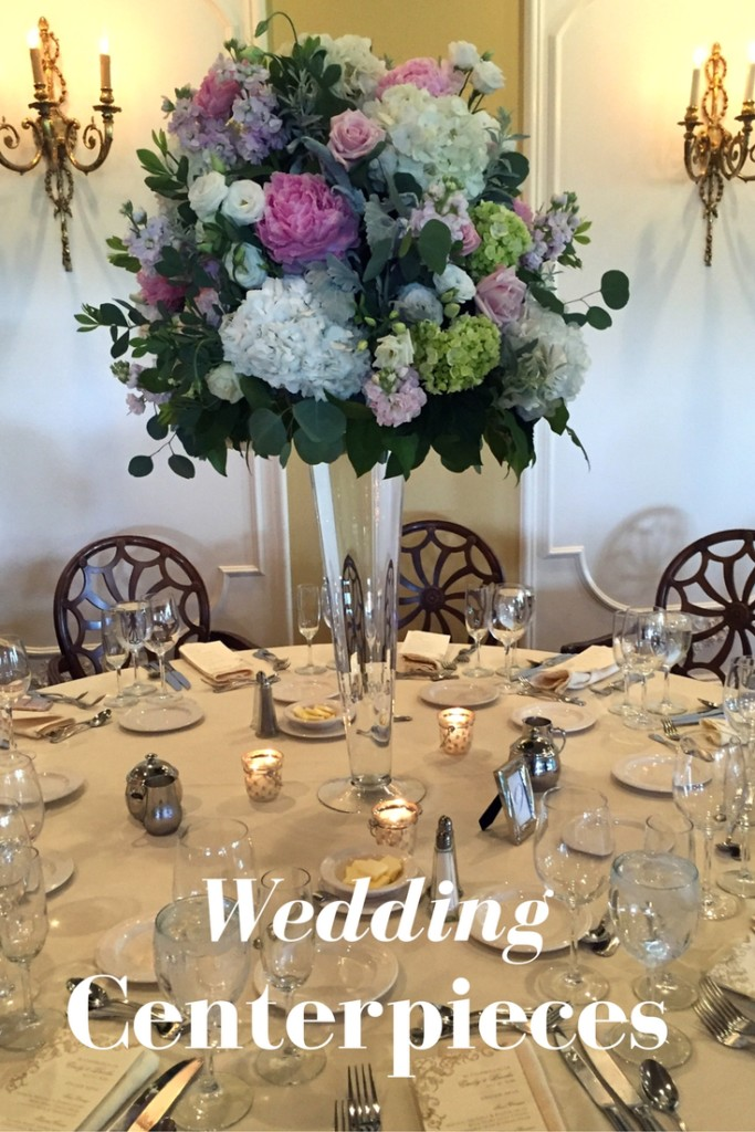 Tall wedding centerpiece in glass trumpet vase with peopnies , hydrangeas and roses with pink and white and blush theme.